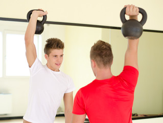 Two young men in gym working out with kettlebells