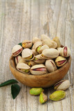 Pistachios with and without shell in wooden bowl with copy space