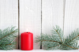 Red candle and branches of blue spruce on wooden background