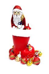 Plastikweihnachtsstiefel mit Schokolade auf weiß isoliert