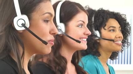 Three customer service representatives talking on headsets
