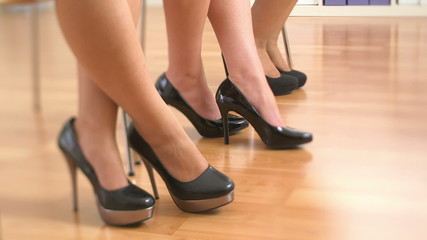 Close up of three business women's feet in high heels standing u
