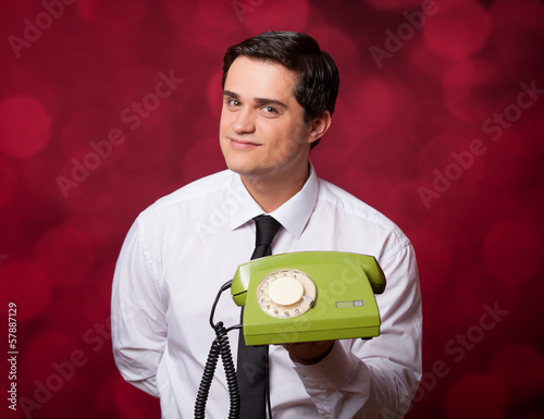 Man with retro phone on red background