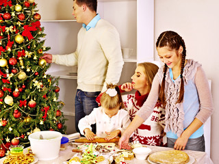Family with children rolling dough in Xmas kitchen.