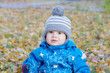 portrait of lovely baby in gray hat in autumn outdoors