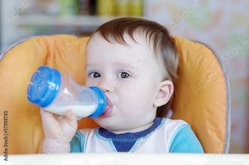 lovely baby drinking milk from a small bottle