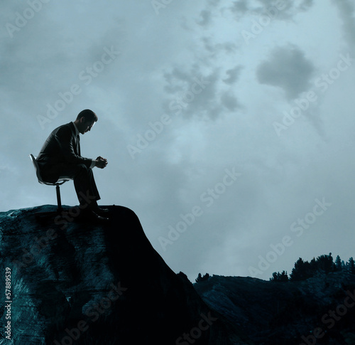 businessman sitting on rock