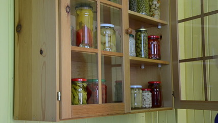 hand open wooden cupboards door puts jar canned garlic