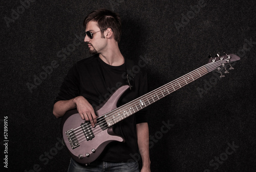 Man standing with bass guitar in studio