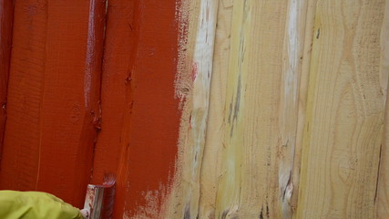 hand yellow glove paint wooden plank wall with brush red color