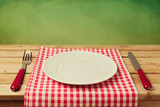 Empty plate with knife and fork on checked tablecloth
