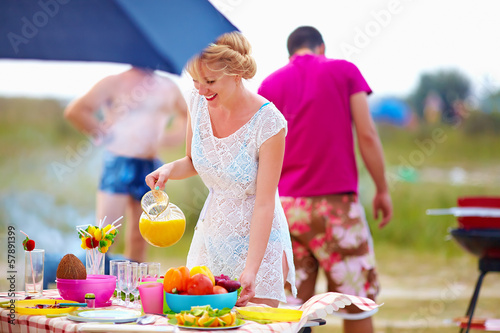happy girl preparing food on picnic table