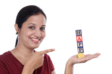 "Happy young woman holding word ""Happy"" of wooden blocks"