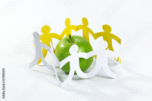 circle of paper people around the green apple