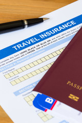 Travel insurance application form with pen and passport