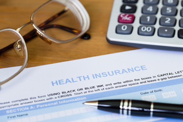 Health insurance application form with pen, calculator, and glas