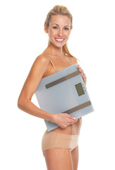 Smiling young woman in lingerie holding scales