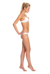 Full length portrait of young woman in lingerie going sideways