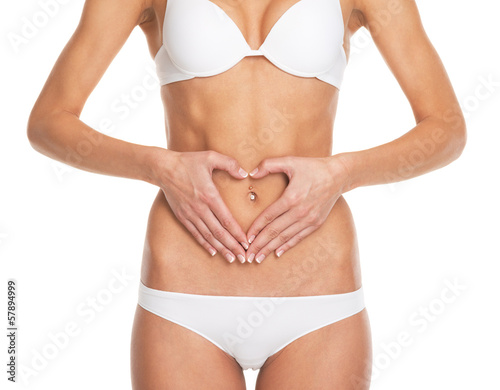Closeup on woman in lingerie put hands on stomach in form heart