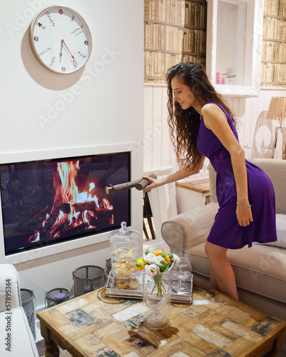 young pretty girl ignites fireplace in the house