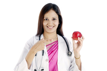Smiling doctor woman showing red apple