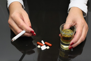 woman hold whiskey and cigarette in hands and drugs on table