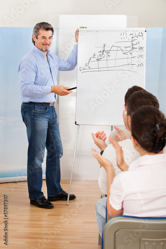 Businessman Explaining Something To Colleagues At Meeting