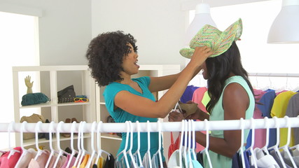 African American friends shopping and trying on hats