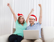 Excited young couple wearing santa hat