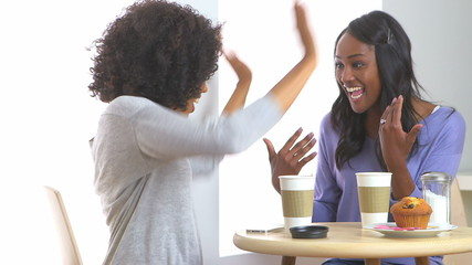 African American woman showing engagement ring to friend in café