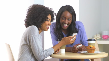 African American friends sharing pictures with mobile phones in