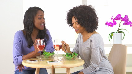 Two African American woman laughing and eating salad together