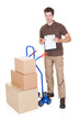 Delivery Man With Clipboard And Boxes