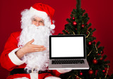 Portrait of a happy santa holding laptop