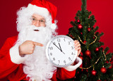 Portrait of a happy santa holding clock