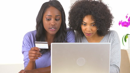 Two African American friends making online purchase with laptop