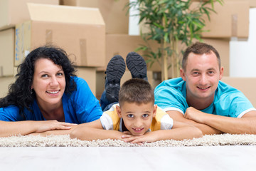 Happy couple with a kid in their new home laying on the floor wi
