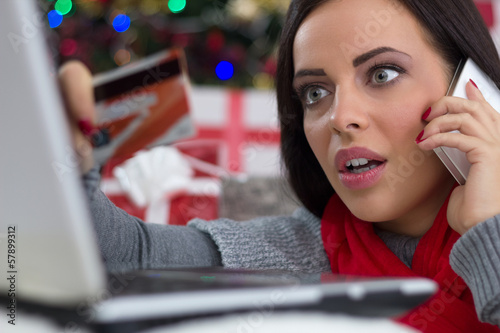 surprised girl in a Christmas night with mobile phone and credit
