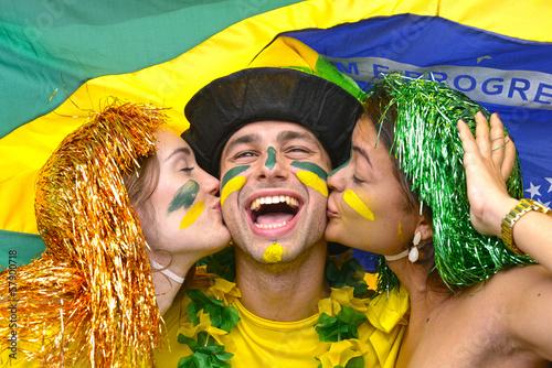 Brazilian soccer fans celebrating victory kissing each other.
