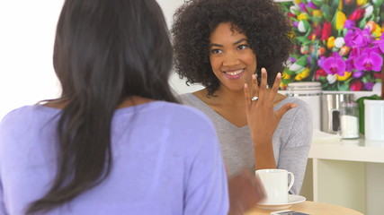 African American woman showing engagement ring to friend