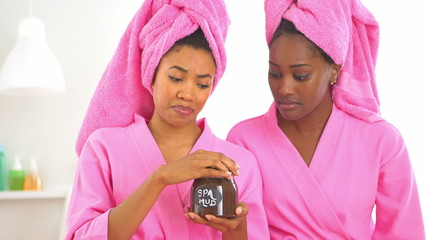 Two African American friends open spa mud and smell it