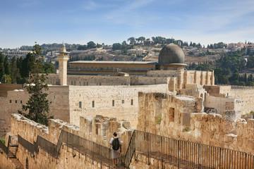 Along the walls of Jerusalem strolls woman pilgrim