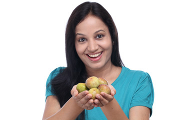 Young woman holding fig fruit in her hands against white