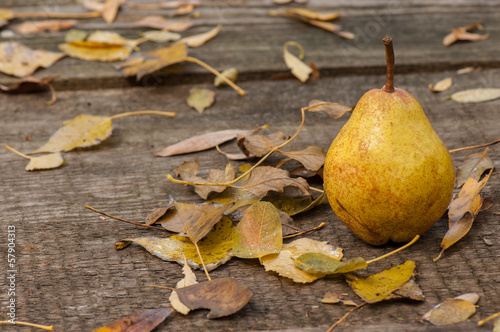 Fresh pears and autumn leaves on a wooden table.