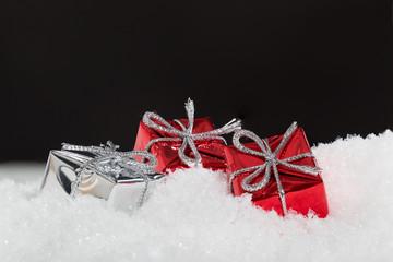 Geschenke im Schnee vor schwarzem Hintergrund