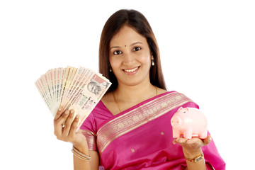 Young smiling Indian traditional woman holding currency and pigg