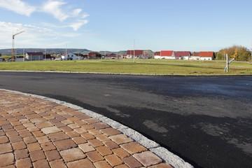 Neue Strasse mit Gehweg aus Betonpflaster im Wohngebiet