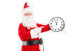 Smiling Santa Claus pointing on a clock