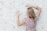 girl stands near a wall with mosaic
