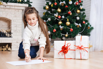 Little girl writes letter to Santa near christmas tree